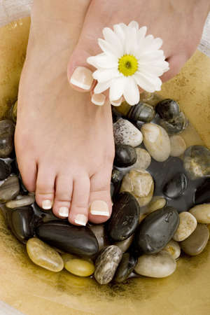 french pedicure: Womans feet in bowl of water and rocks Stock Photo