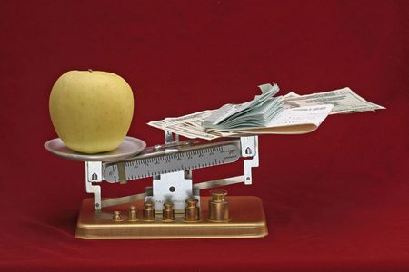 later: Balance scale showing how the apple, a symbol of prevention and health, outweighs the money spent to get better after sickness.  Pay now or pay later.