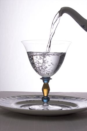 emphasizes: Clear water being poured into a stylish goblet.  Light shining through emphasizes purity