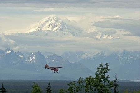 denali: A view of Mt. McKinley (Denali) in Alaska with plane coming in for a landing as seen from Talkeetna, Alaska Stock Photo