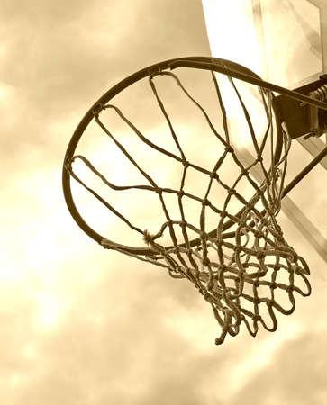 Basketball hoop against a cloudy sky. Sepia tone photo