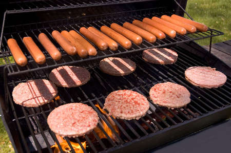Gas grill loaded with hotdogs and hamburgers.