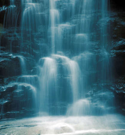 A close-up of a beautiful waterfall with a blue cast to it for effect. Very cooling and peaceful feel. Nice background image.
