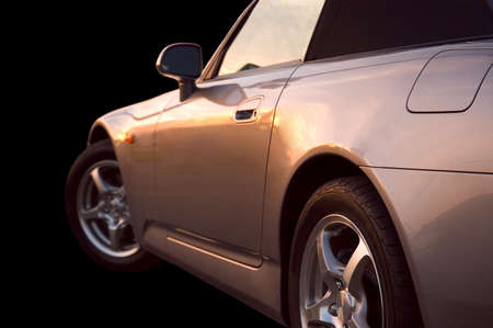 A sportscar with the glow of the sunset refecting on its paint. Stock Photo