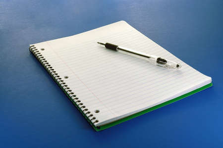 ruled: A notebook and pen close-up on a blue background. Stock Photo