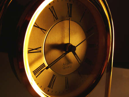 ambient light: Old style mantel clock with roman numerals in ambient light. Stock Photo