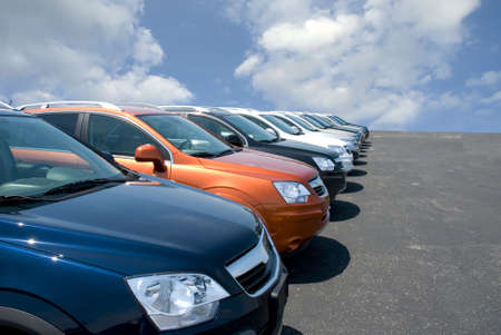 new car lot: New fuel efficient SUVs on a car dealers lot for sale.  Stock Photo