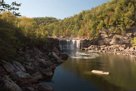 roped off: Wide view of Cumberland falls in Kentucky.  This waterfall  is located near the city of Corbin in Cumberland falls state park.  For scale you can see people standing at the left side of the falls in a roped off viewing area. Photo was taken in mid October