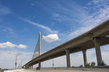 skyway: A view of the Veterans  Glass City Skyway bridge in Toledo Ohio  A beautiful blue sky with white clouds for a background