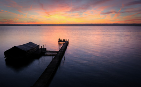 shores: A beautiful autumn sunrise on the shores of Lake Cayuga in the Finger lakes region of New York state   The peir leads out to a power boat shelter and a deck with chairs for watching the sunrise  Stock Photo