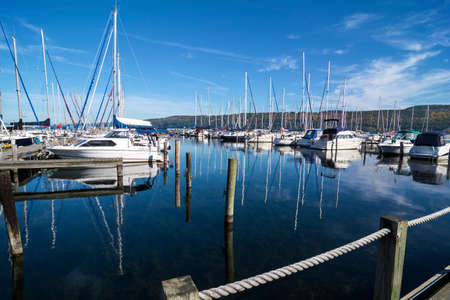 Lots of sails boats at the boat marina harbor at the southern end of Seneca lake in Watkins Glen New York on a beautiful blue sky day in autumn