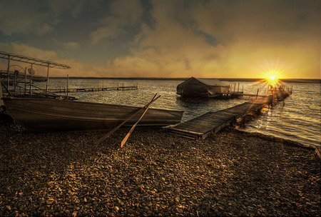 A beautiful autumn sunrise on the shores of Lake Cayuga in the Finger lakes region of New York state. A row boat with oars is docked on the side of a peir that leads out to a power boat shelter and a deck with chairs for watching the sunrise.