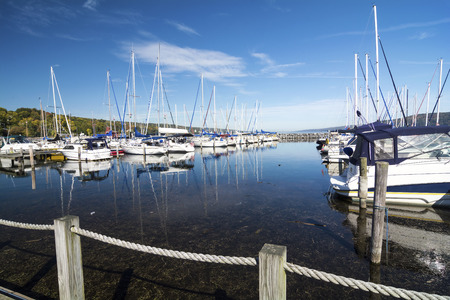 seneca: Lots of sails boats at the boat marina harbor at the southern end of Seneca lake in Watkins Glen New York on a beautiful blue sky day in autumn.