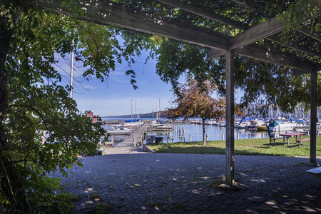 seneca: A look from under a pergola at sails boats at the boat marina harbor at the southern end of Seneca lake in Watkins Glen New York on a beautiful blue sky day in autumn.