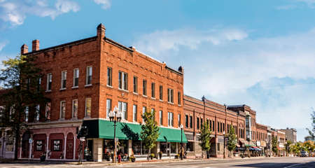architecture and buildings: A photo of a typical small town main streetin the United States of America. Features old brick buildings with specialty shops and restaurants. Decorated with autumn decor.  Stock Photo