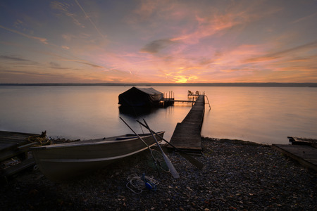 shores: A beautiful autumn sunrise on the pebbled shores of Lake Cayuga in the Finger lakes region of New York state  A row boat with oars is docked on the side of a peir that leads out to a power boat shelter and a deck with chairs for watching the sunrise