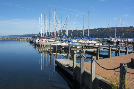seneca: Sail boats at the boat marina at the southern end of Seneca lake in Watkins Glen New York on a beautiful blue sky day in autumn