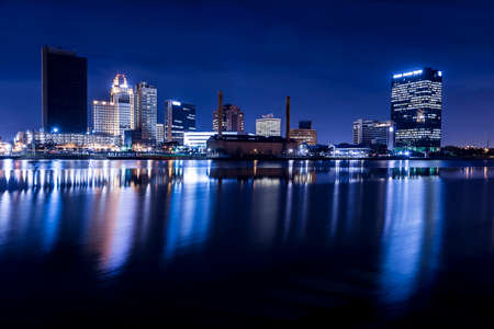 A panoramic view of downtown Toledo Ohio at night with the lights reflecting into the Maumee river  Stock Photo