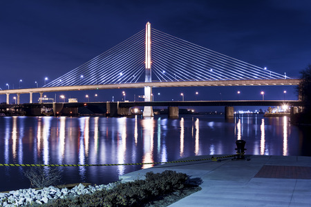 Night view of the Veterans  Glass City Skyway bridge in Toledo Ohio   The bridges center pylon is lit up with LED lighting and the stainless steel cables are lit with floodlights