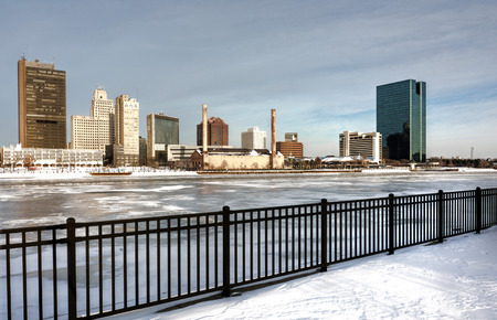 A view of downtown Toledo Ohio s skyline from across the frozen and snow covered Maumee river  A beautiful partly cloudy blue sky makes for a pretty winter scene  photo