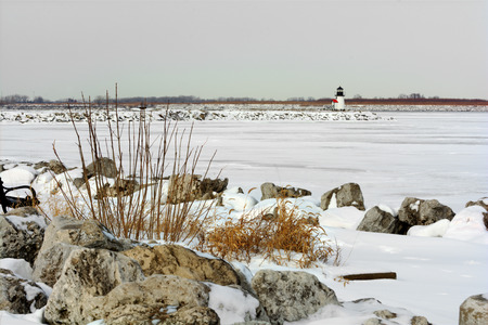 erie: A small lighthouse at the entrance to the port of Toledo Ohio in winter  Lake Erie is frozen and covered with snow in this winter scene