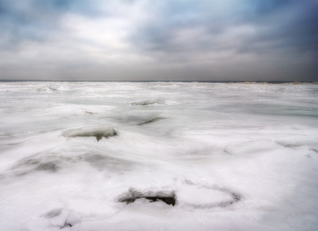 The frozen, ice and snow covered Lake Erie In Northwest Ohio  The sun is hidden behind a thick layer of storm clouds  Stock Photo