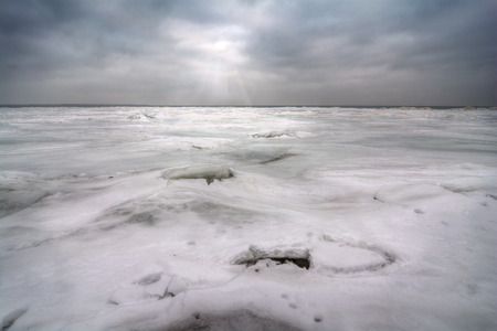 frozen lake: The frozen, ice and snow covered Lake Erie In Northwest Ohio  The sun is breaking through the clouds with sun rays and two ice fishing holes can be seen in the foreground   Stock Photo