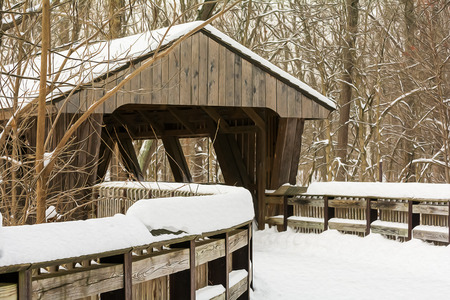 Winter scene with a winding wooden boardwalk leading to a covered bridge that crosses  a river in a wooded park.  photo