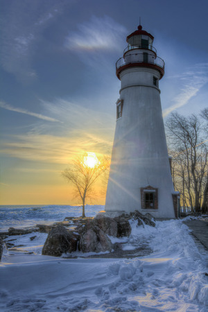 winter: The historic Marblehead Lighthouse in Northwest Ohio sits along the rocky shores of Lake Erie  Seen here at sunrise in winter with snow and ice on the ground  Stock Photo