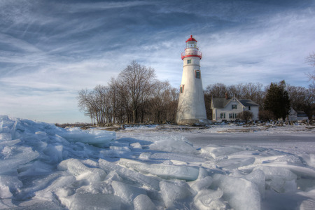 The historic Marblehead Lighthouse in Northwest Ohio sits along the rocky shores of Lake Erie  Seen here from out on the frozen lake where large chunks of ice have piled up near shore  Stock Photo
