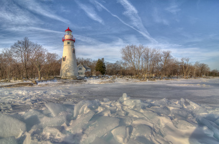 erie: The historic Marblehead Lighthouse in Northwest Ohio sits along the rocky shores of Lake Erie  Seen here from out on the frozen lake where large chunks of ice have piled up near shore  Stock Photo