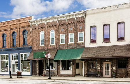 historic architecture: A photo of a typical small town main street in the United States of America  Features old brick buildings with specialty shops and restaurants  Decorated with spring flowers and American flags