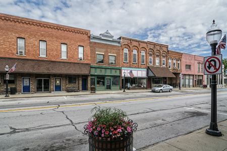 small country town: A photo of a typical small town main street in the United States of America  Features old brick buildings with specialty shops and restaurants  Decorated with spring flowers and American flags