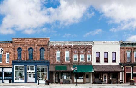 main street: Una foto di una tipica strada principale cittadina degli Stati Uniti d'America Caratteristiche vecchi edifici in mattoni con negozi specializzati e ristoranti decorati con fiori e bandiere americane Archivio Fotografico