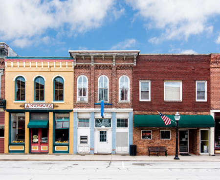 small town: A photo of a typical small town main street in the United States of America  Features old brick buildings with specialty shops and restaurants  Decorated with  American flags