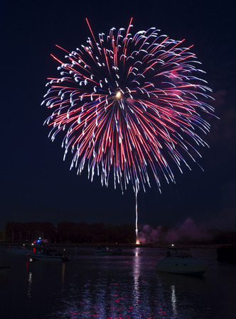 boat party: Photo of colorful, exploding fireworks in the night sky during a July 4th holiday celebration in Toledo Ohio Taken  along the Maumee river with boats and colorful reflections in the water  Stock Photo