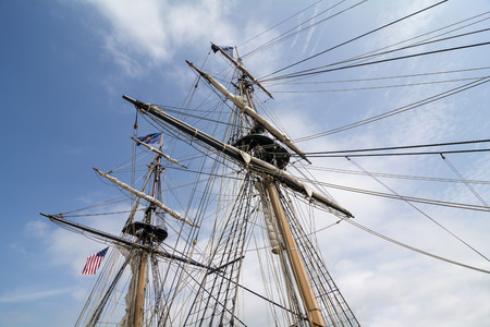 brig: The masts and rigging of the tall ship U.S. Brig Niagara against a blue, cloud filled sky. Stock Photo
