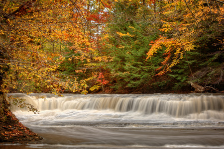 Beautiful autumn colors on the trees frame this broad waterfall.  The waterfall is called Quarry Rock Falls and is found in the South Chagrin Reservtion of the Cleveland Ohio Metroparks. Stock Photo