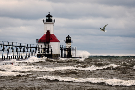 A small lighthouse out on a pier in St. Joesph Michigan during stormy weather with waves crashing into the pier and a seagull flying by. photo