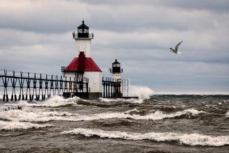 lake michigan lighthouse: Un pequeño faro en un muelle en San Joesph Michigan durante una tormenta con olas chocando en el muelle y una gaviota volando. Foto de archivo