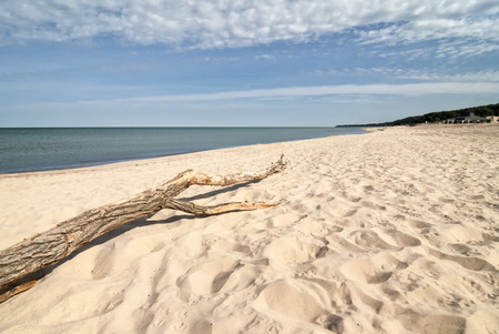 Looking down the white sand beach on Lake Michigan near St. Joesph Michigan. A drift wood log rests on the beach, Beautiful clean sand stretches for as far as the eye can see.