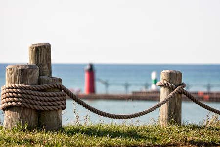 lake michigan lighthouse: Foto de postes de madera con una cuerda tendida entre ellos con el lago Michigan y un faro en el fondo. Focus es intencionalmente poco profunda y está en la cuerda y mensajes.