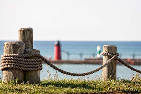 Photo of wooden posts with rope strung between them with Lake Michigan and a lighthouse in the background. Focus is intentionally shallow and is on the rope and posts.