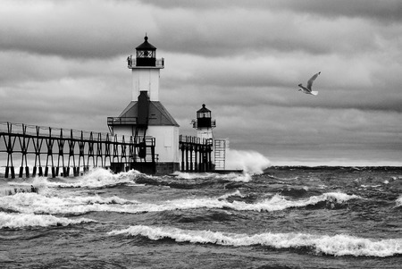Black and white photo of a small lighthouse out on a pier in St. Joesph Michigan during stormy weather with waves crashing into the pier and a seagull flying by. photo