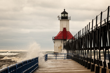 lake michigan lighthouse: Un pequeño faro en un muelle en San Joeseph Michigan durante una tormenta con olas rompiendo en el muelle.