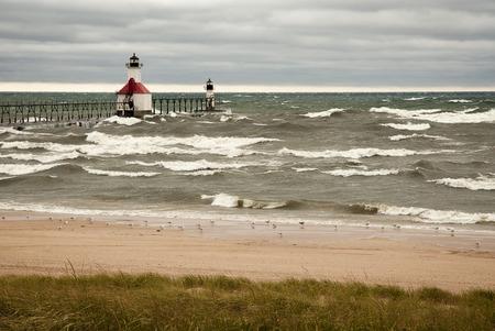 lake michigan lighthouse: Un peque�o faro en un muelle en San Joesph Michigan durante una tormenta con olas del lago Michigan golpeando contra ella. Foto de archivo