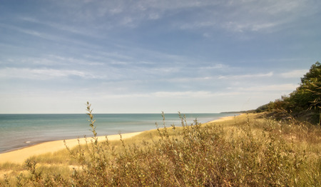 Looking down the white sand beach on Lake Michigan near St. Joesph Michigan. Beautiful clean sand stretches for as far as the eye can see.