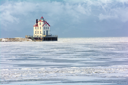 frozen lake: The Lorain Lighthouse is a historic landmark on the shores of Lake Erie, one of the Great Lakes. Seen here in winter with snow and ice.