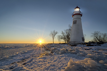 winter sunrise: The historic Marblehead Lighthouse in Northwest Ohio sits along the rocky shores of the frozen Lake Erie. Seen here in winter with a colorful sunrise and snow on the ground.