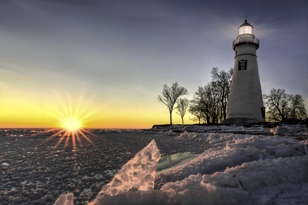 winter sunrise: The historic Marblehead Lighthouse in Northwest Ohio sits along the rocky shores of Lake Erie. Seen here in winter at sunrise.